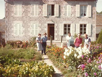 Promenade au jardin en fleurs et légumes de légumes (on aperçoit les hautes tiges des asperges) après le repas de famille par jour de canicule car contrevents fermés.