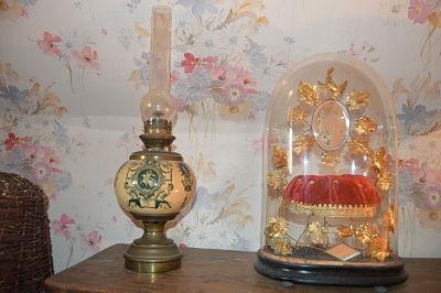 Près de la jolie lampe à pétrole, trônaient, empoussiérés, des globes de mariée dont celui-ci, de maman, à l'intérieur duquel, la fraîche épousée déposait, au soir des noces, s